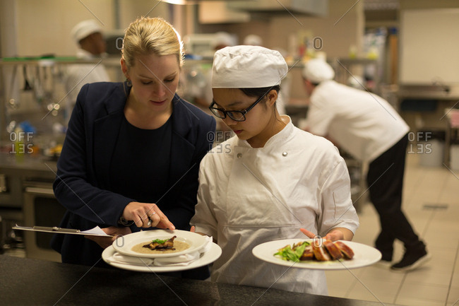 Female manager and female chefs interacting with each other in kitchen