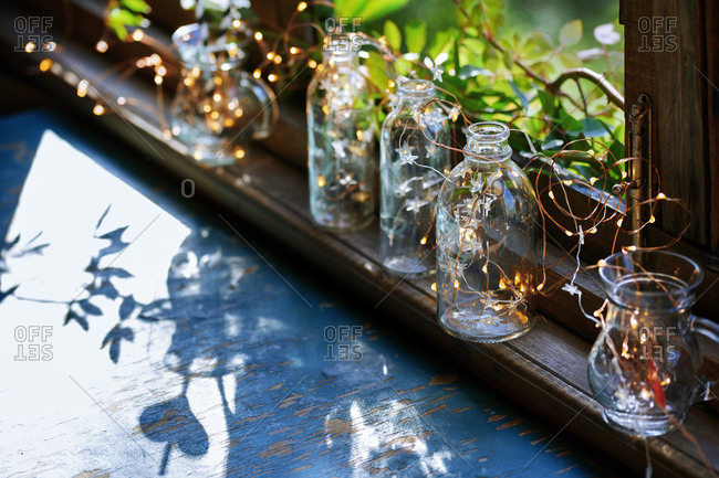 Window sill decorated with glassware and Christmas string light