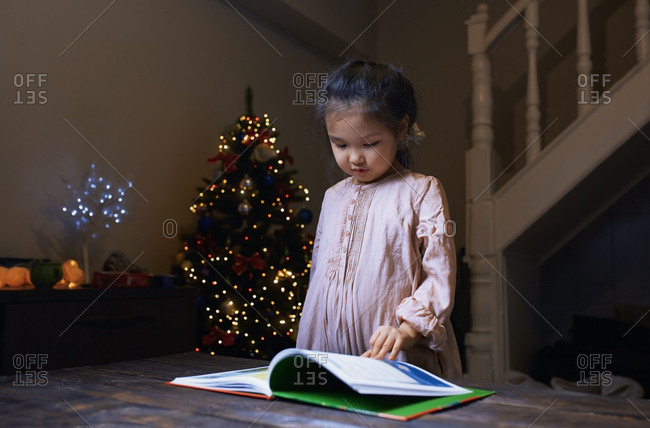 Cute girl reading book at home decorated for Christmas holiday