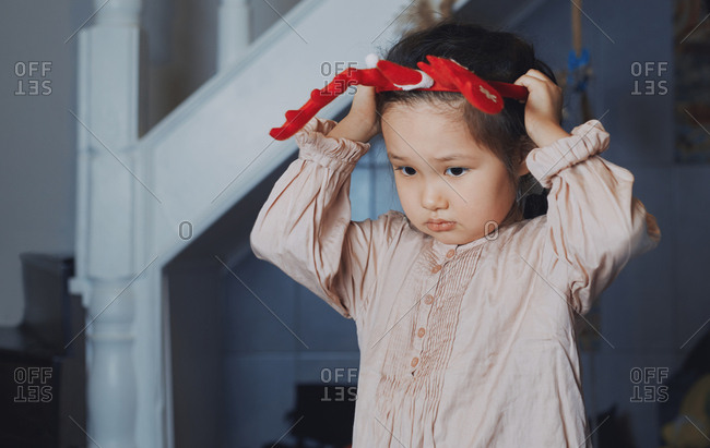 Cute girl at home putting on Christmas reindeer antlers