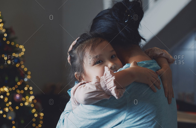 Hugging mother and daughter at home decorated for Christmas holiday
