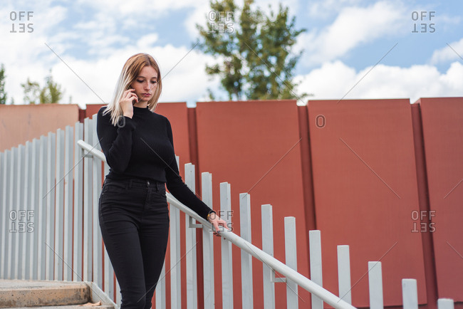 Young woman walking and talking on cell phone