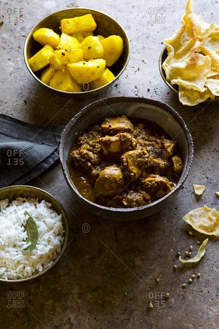 Bowls of chicken tikka masala, rice, and papadum