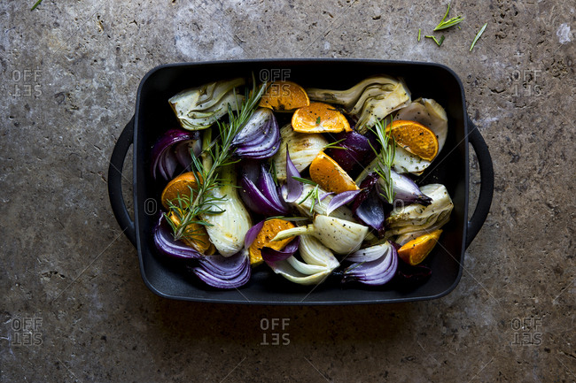 Overhead view of fennel, red onion and orange slices in a roasting pan