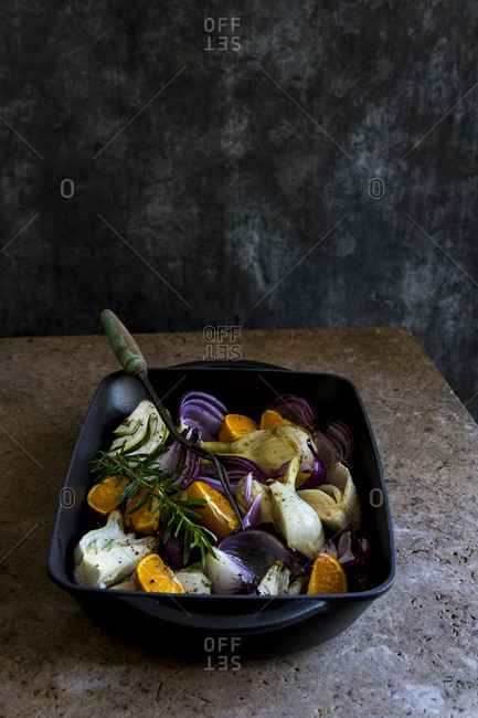 Fennel, red onion and orange slices in a roasting pan