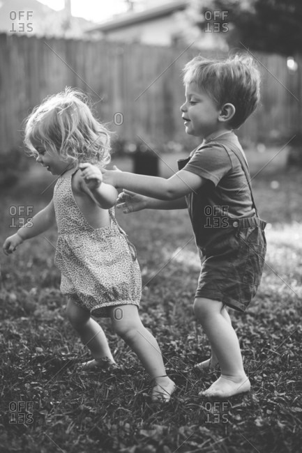 Toddler siblings playing in backyard in black and white
