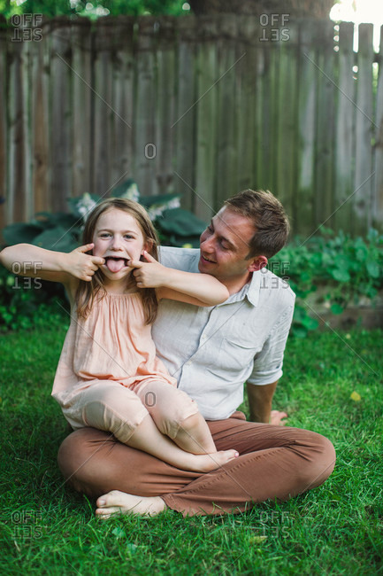 Little girl making silly faces while sitting in dad's lap
