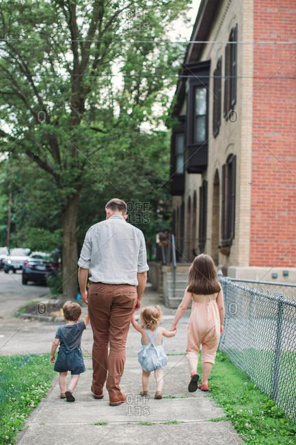 Kids walking on sidewalk hand in hand with dad