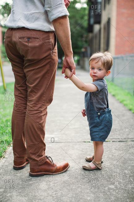Little boy walking on sidewalk hand in hand with dad