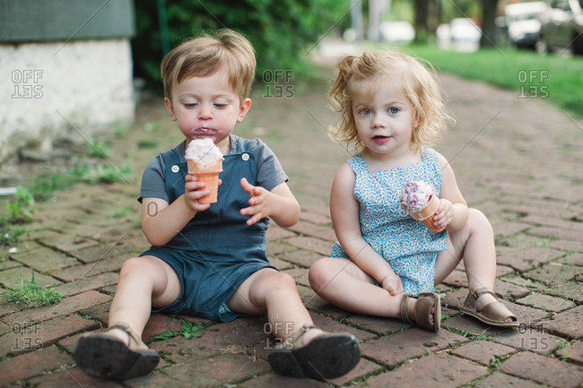 Two toddlers on ground eating ice cream
