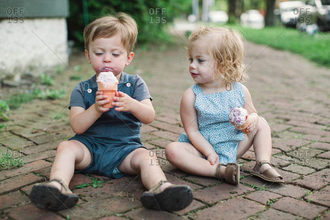 Two toddler siblings sitting on ground eating ice cream
