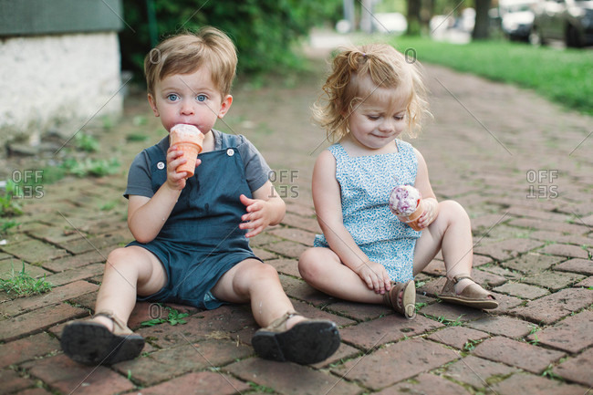 Toddlers sitting on ground eating ice cream