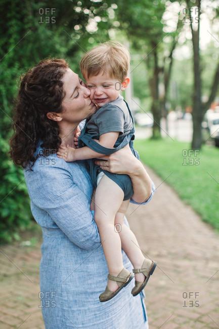 Mother kissing toddler boy