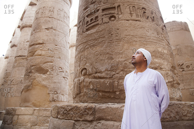 Egyptian guide posing near ancient column