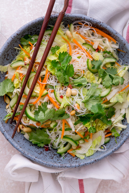 Vegetarian salad with rice noodles, fresh vegetables, cilantro and peanuts. Thai cuisine style, diet healthy meal