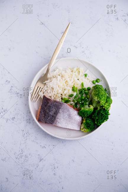 Cooked salmon with basmati rice, broccoli and beans on concrete background. Healhy nutrition concept