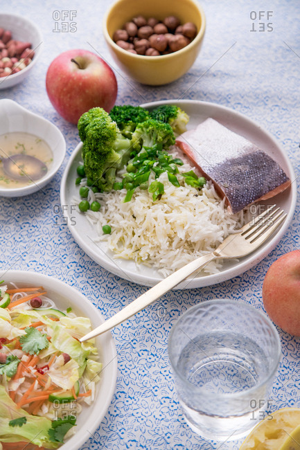 Healthy dinner with rice noodle salad, cooked salmon with basmati rice, broccoli and beans.
