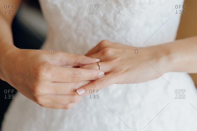 Faceless shot of elegant bride putting on elegant engagement ring