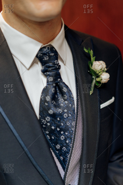 Crop man in elegant groom suit with ornamental tie and white boutonniere