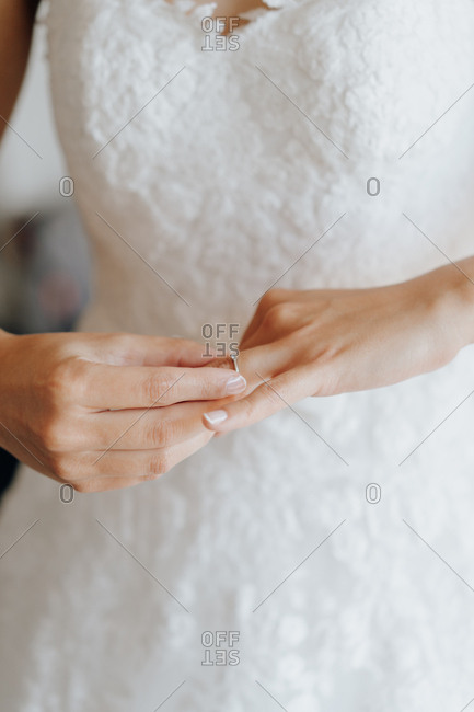 Crop bride putting on engagement ring