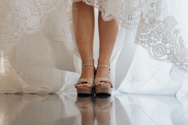 Crop shot of female legs in high heels and bridal white lace dress standing on shiny floor