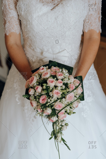 Crop woman in lace bridal dress holding beautiful green bouquet with pink roses