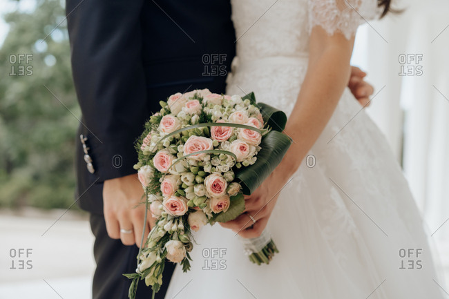 Crop side view of bride holding pink bouquet and kissing with groom outdoors
