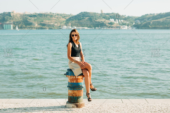Trendy woman at seafront with sitting with water in the background