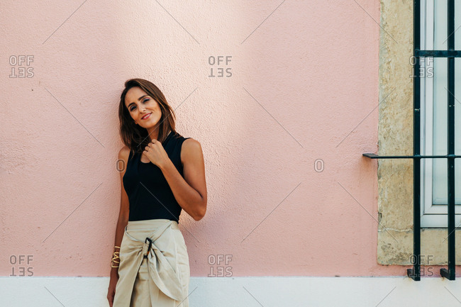 Charming adult brunette in trendy outfit leaning on wall on street looking at camera