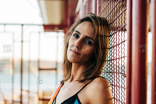 Side view of content adult woman leaning on metal wire fence outdoors looking at camera in sunlight