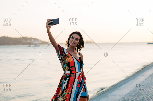 Content woman in dress using phone and taking selfie on seafront in sunset time