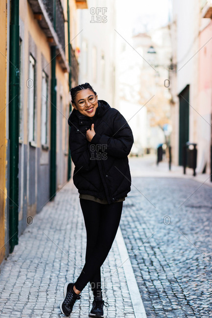 Beautiful content woman cuddling in black warm coat standing on cobblestone street and laughing