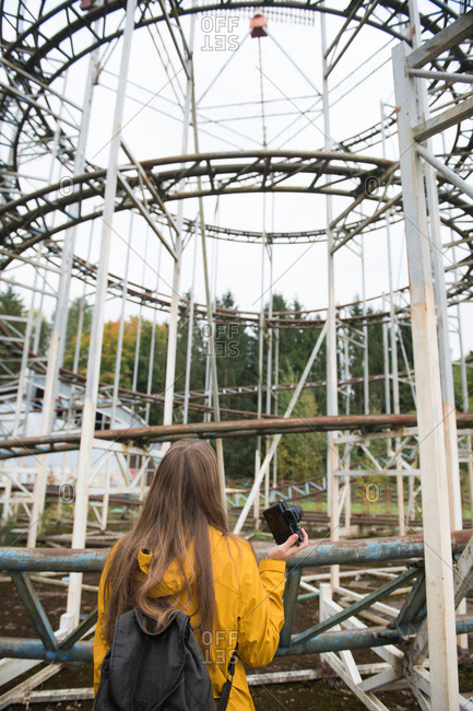 Back view of blond woman with camera taking photo of desolated amusement park with attractions