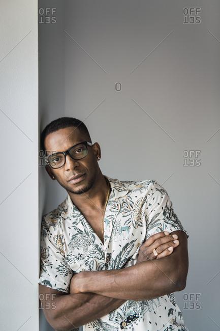 Casual black man leaning on white wall near window