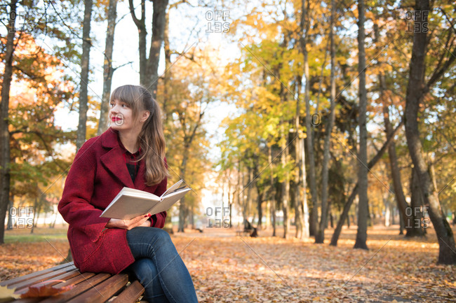 Attractive young��?lady in red coat holding opened volume, sitting on seat and looking away in autumn forest
