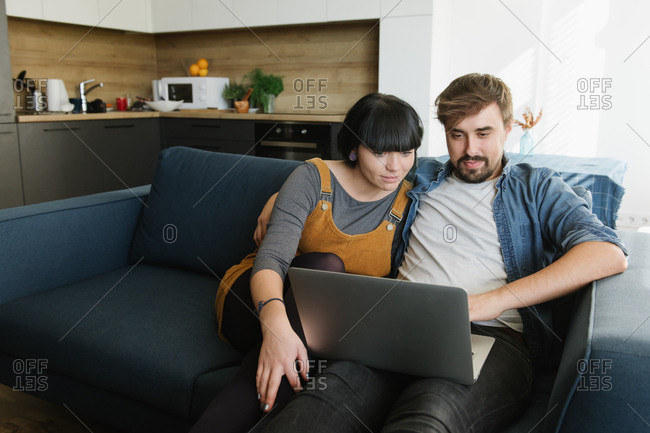 Young man and woman embracing each other and enjoying good film on laptop while sitting on comfortable sofa in cozy living room