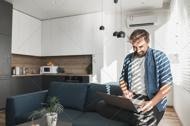 Bearded guy browsing modern laptop while sitting on comfortable couch in stylish living room