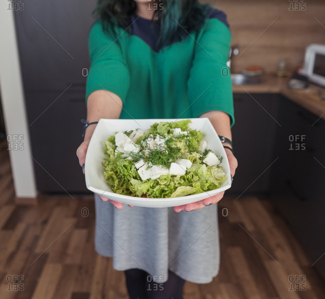Crop female in casual dress demonstrating bowl with fresh salad to camera while standing in stylish kitchen at home