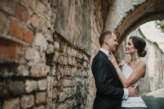 Married couple hugging near old wall