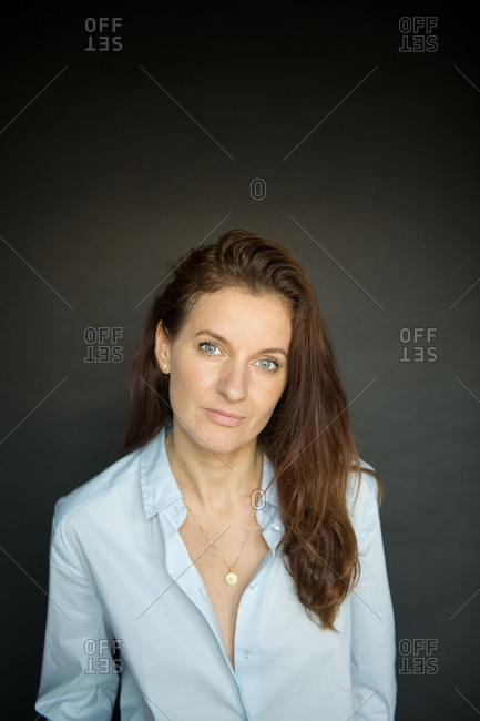 Attractive adult female in elegant blouse smiling and looking at camera while standing on black background