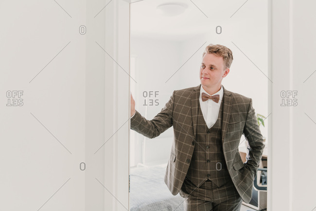 Handsome young guy in elegant wedding suit smiling and looking away while standing in doorway of stylish room
