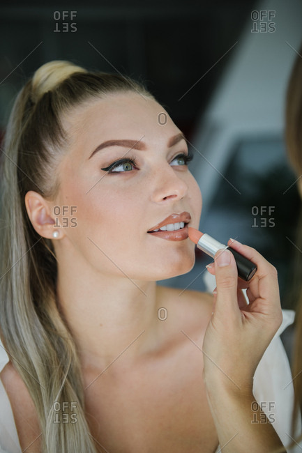 woman applying make up on a bride