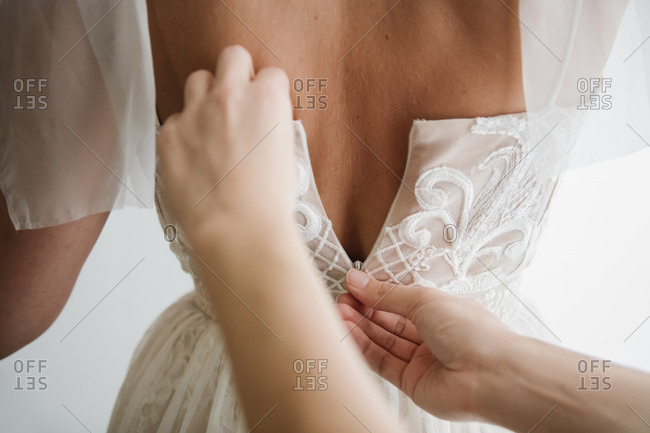 Crop hands of person helping to bride to zip white gown