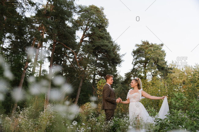 Groom holding hand of the bride in a forest