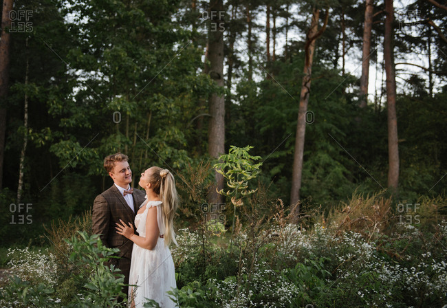 Wedding couple looking each other in the forest