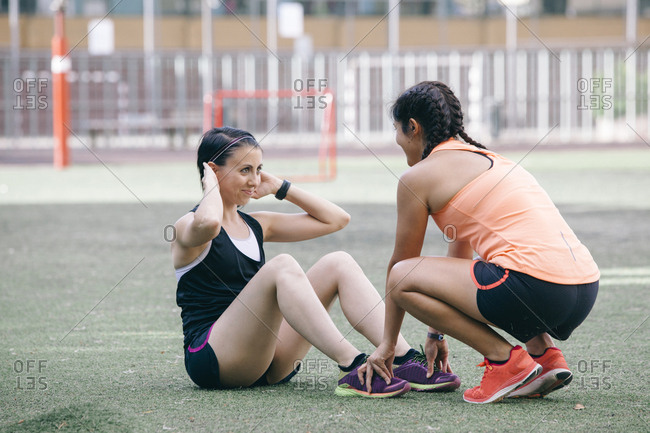 Supporting sportswomen working out together on stadium and training abdomen muscles