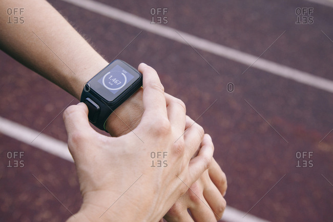 Crop shot of female hands wearing smart watch and using device on racetrack
