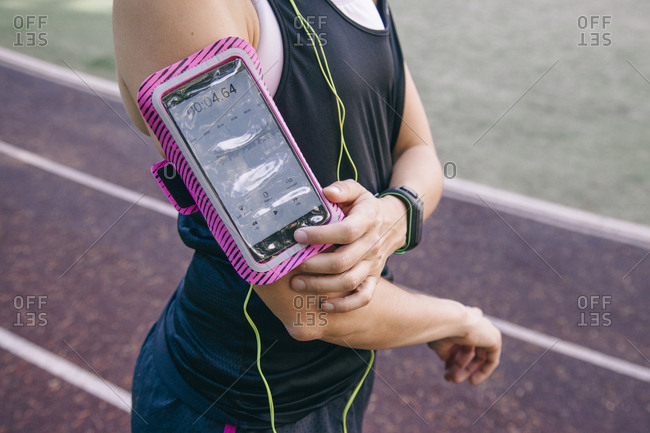 Faceless shot of woman in sportswear wearing armband with smartphone and listening to music on racetrack
