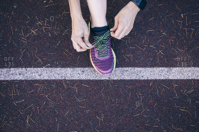 Crop shot from above of woman tying sneaker shoelace on rubber racetrack