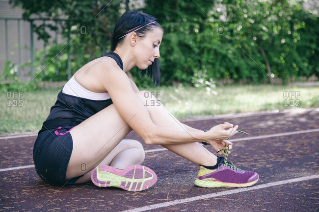 Side view of sportswoman sitting on rubber racetrack and tying shoelace before workout